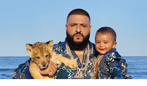 DJ Khaled posing with a baby human and a baby lion